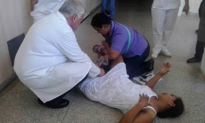 """Una mujer embarazada se dirigió al Hospital de Uyapar de Ciudad Guayana, en el estado Bolívar, en busca de ayuda médica para dar a luz; pero la falta de insumos obligó al personal de guardia a rechazar su ingreso lo que trajo como consecuencia que tuviera a su bebé en el pasillo de ese centro asistencial. En vista de que el Servicio de Ginecología no contaba con los insumos para hospitalizarla, la mujer se sentó en el pasillo del hospital, estando allí tuvo a su bebé, acostada sobre el piso. El jefe de Cirugía del hospital, el doctor Rosario, iba pasando por el lugar y ayudó a la mujer con el parto, informó el periodista Germán Dam, en su cuenta en Twitter (@GEDV86). Mientras la atendía, el médico le decía """"vas a parir, pero no vas a parir sola""""."""